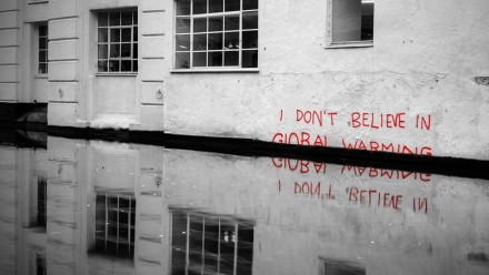 A graffiti piece saying 'I don't believe in global warming' only half visible above a rising waterline.