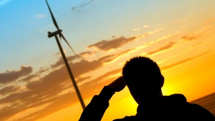 A person standing next to some wind turbines looks out into the sunset.