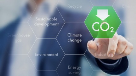 "Man points to a hexagon shape with the word ""CO2"". Other hexagons say climate change, sustainable development, greenhouse gas, recycle, industry, environment and energy saving."