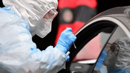 A person in full personal-protective-equipment leans into a car window to conduct a COVID-19 test swab.