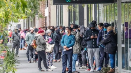 A large queue of people wearing hygiene masks outside Centrelink offices in Melbourne.