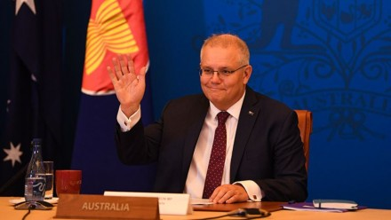 A photograph of Scott Morrison, sitting behind a desk with a plaque reading 'Australia' at the front, raising his hand in a wave and smiling.