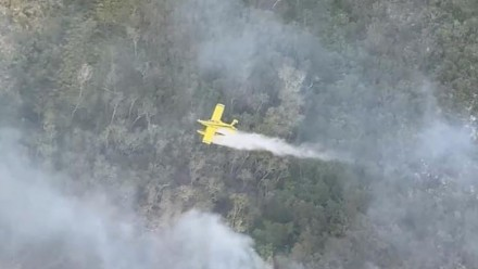A plane drops water over bushfires on Fraser Island, Queensland, Australia, November 27, 2020.