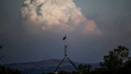 A photograph of Australia's Parliament House with a huge plume of bushfire smoke rising in the distance.