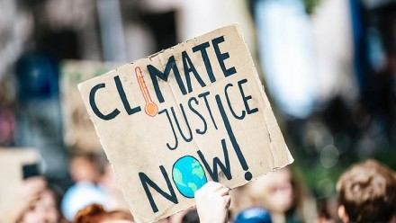 A photograph of a person's hand holding up a sign reading 'Climate justice now'.