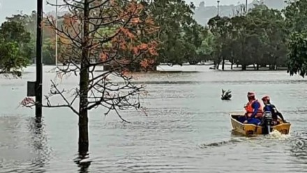 SES crew members in a small boat, sailing through flood waters in a suburban area.