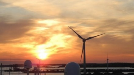 The sun sets behind a wind turbine, with a large body of water on the lefthand side.