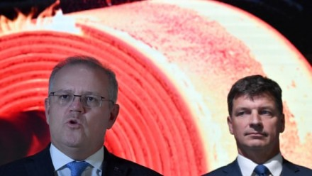 A photograph of Scott Morrison giving a presentation, with Angus Taylor standing behind him to his right.