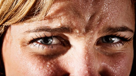 A woman's face, sweating profusely.