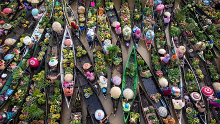 An aerial image of many small boats crowded together, carrying farm produce.
