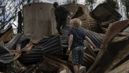 Ian Livingston and his son Sydney, 6, among the ruins of their family home, lost to the New Year's Day bushfires in Cobargo.