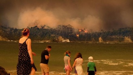 Evacuees on a beach look on as bushfire burns through the NSW south coast township of Malua Bay.
