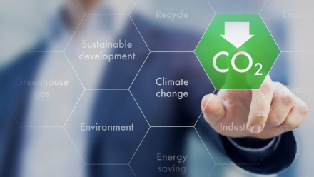 A person's hand, with a finger pointing to a green hexagon on a screen with the CO2 sign written underneath a downwards pointing arrow - indicating a decrease in carbon dioxide. Around this are other hexagons with words such as 'sustainable development'.