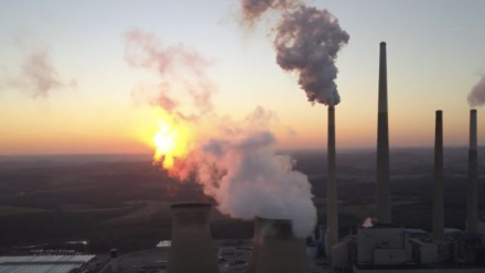 The sun sets behind a coal-fired power station.