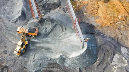 An aerial view of a tractor moving coal into the back of a truck in an open cut mine.
