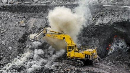 A yellow tractor shovels coal in an open cut mine.