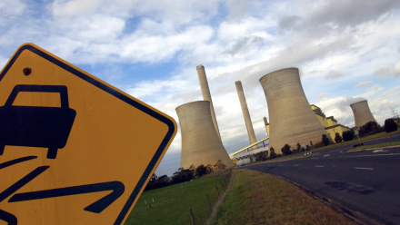 A 'windy road' road sign, with a coal-fired power station in the background.
