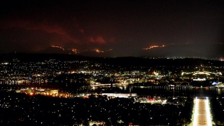 An image looking over Canberra at night time on 31 Jan 2020, with the hills in the background lit up orange with the Orroral Valley fire burning.