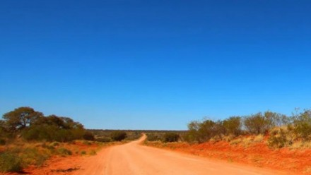 A photograph of a dirt road in outback Australia, leading through a desert area of red sand and bushes.
