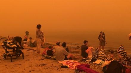 Isobel Davis' family on the beach at Batehaven, shrouded in orange bushfire haze, after having lost her parents' house to the bushfires.