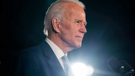 A picture of Joe Biden dressed in a suit, looking to the right of the camera, with a dark background and a light shining up from the bottom of the image.