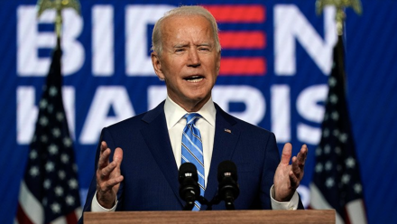 A photograph of Joe Biden delivering a speech, with the 'Biden - Harris' presidential campaign poster in the background.