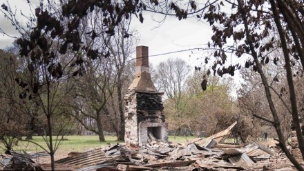 A fireplace remains standing in the rubble of a burnt property.