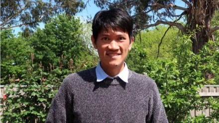 A photograph of Phd Scholar Phaothai Sin-Ampol, smiling and looking towards the camera, while outside on a sunny day.