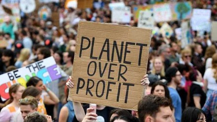 A sign reading 'Planet over profit' is held up at a Global Strike 4 Climate rally in Melbourne in September 2019.