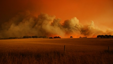 A fire at Churchill, Victoria on Black Saturday 2009. The sky is a dark orange colour, with a thick plume of smoke rising in the distance from where the fire is burning.