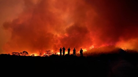 A photograph of an immense bushfire, with the silhouettes of five firefighters standing on a hill in the forefront of the blaze.
