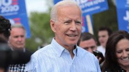 A photograph of Joe Biden, smiling and looking towards the camera, with some of his supporters in the background holding campaign posters.