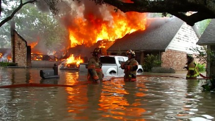 A house on fire, whilst also sitting in flood waters, with two fire fighters standing in the front.