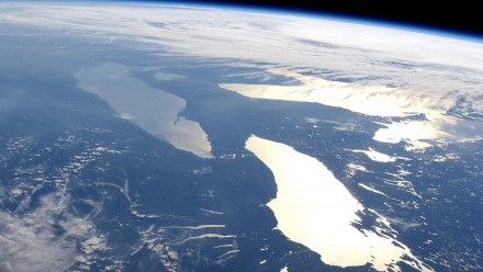 A photograph of Earth from outer space, with sunlight beaming off the ocean.