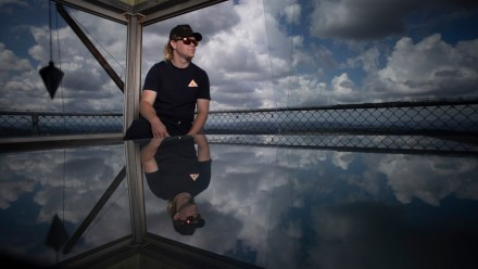 Nick Dutton, fire tower operator, Rural Fire Service in the Kowen Forest fire tower near Canberra. Nick is wearing a cap and sunglasses, and looking to the right. The sky behind him is cloudy.