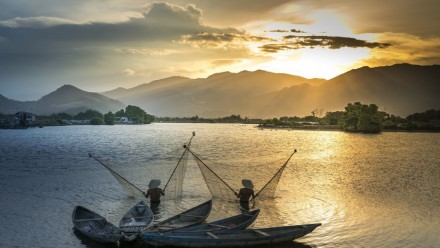 The sun sets behind mountains in the distance, with the two people fishing in the Mekong River Basin in the foreground.