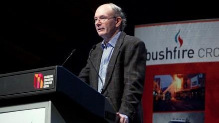 A photograph of Em Prof John Handmer delivering a presentation