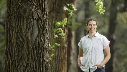 Dr Adele Morris standing next to a large tree in a forested area, looking at the camera and smiling