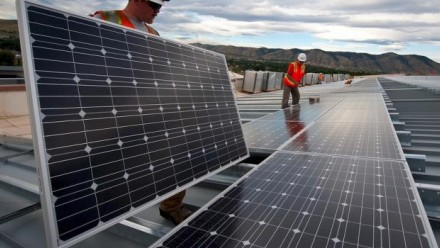 Workers holding solar panels