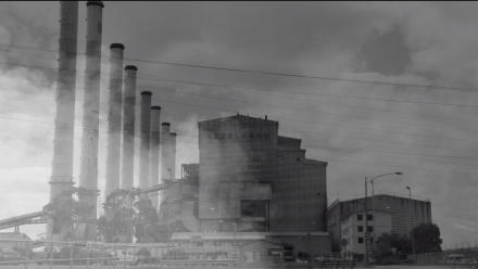 A video still projected onto a wall in Canberra's city centre shows a black and white image of a coal mine, with clouds superimposed over it.