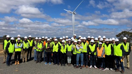A group of students in high-vis vests and hard hats standing in front of a wind turbine.