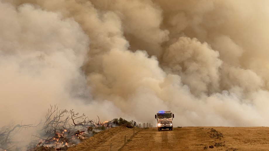 A fire truck drives along a dirt road, in front of a huge cloud of smoke.