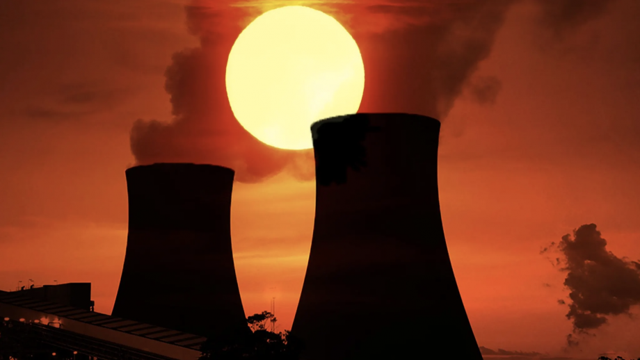 The sun sets behind a coal-fired power station
