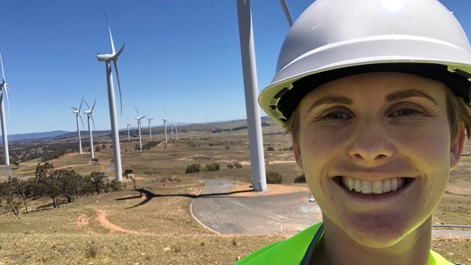 Master of Climate Change student, Caitlin Sears, standing in front of wind turbines