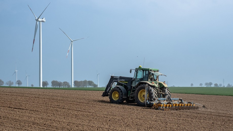 A tractor on a crop with wind turbines in background