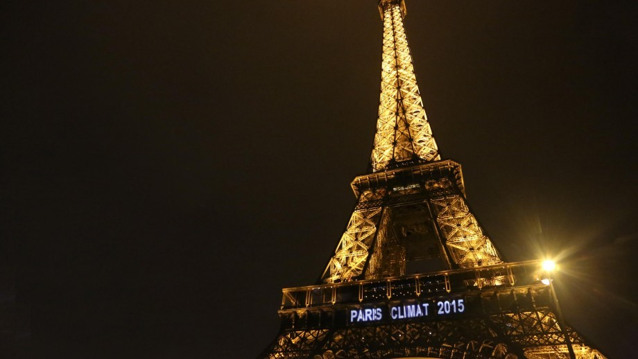 The Eiffel Tower at night, with the words 'Paris Climat 2015' lit up on it.