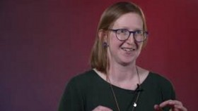 A picture of Dr Bec Colvin during her TEDxCanberra speech, wearing a green dress and glasses, with a maroon background.