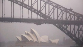 A photograph of the Sydney Opera House in the background, and the Sydney Harbour Bridge in the foreground, on a misty and rainy day.