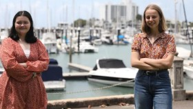 Teenagers Brooklyn O'Hearn and Claire Glavin from North Queenslad standing 1.5 metres apart, with their arms crossed, smiling and looking towards the camera. There are small ships docked at a pier behind them.