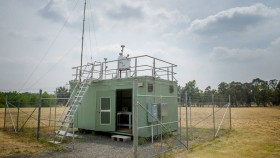 A light green air monitoring station in Canberra, sitting in the middle of a field of dry grass.